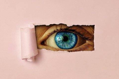 Auge blickt durch Papier
